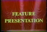 Still frame from: Drive-in: Feature Presentation- Red curtain-Searchlights