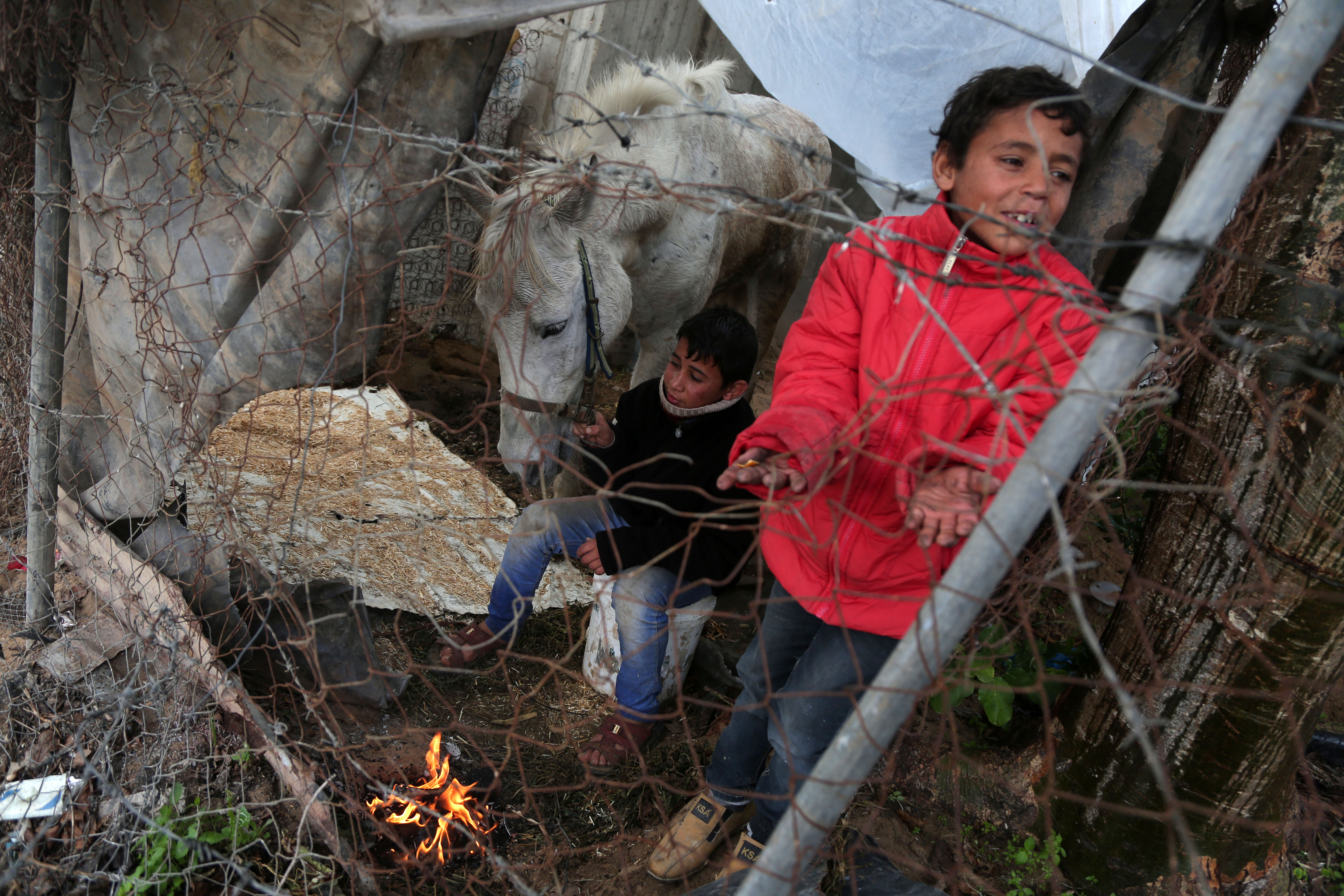 Palestinian children warm up in front of a fire in a hovel